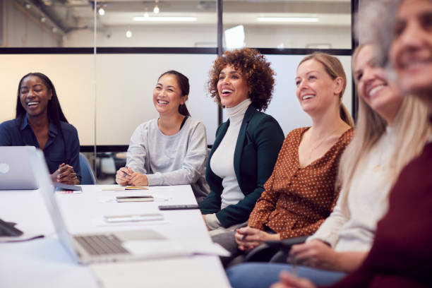 Line Of Businesswomen In Modern Office Listening To Presentation By Colleague stock photo
