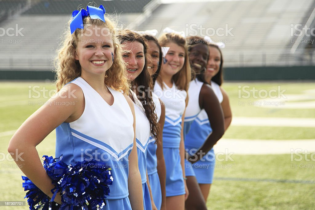 line of cheerleaders wearing blue and white stock photo