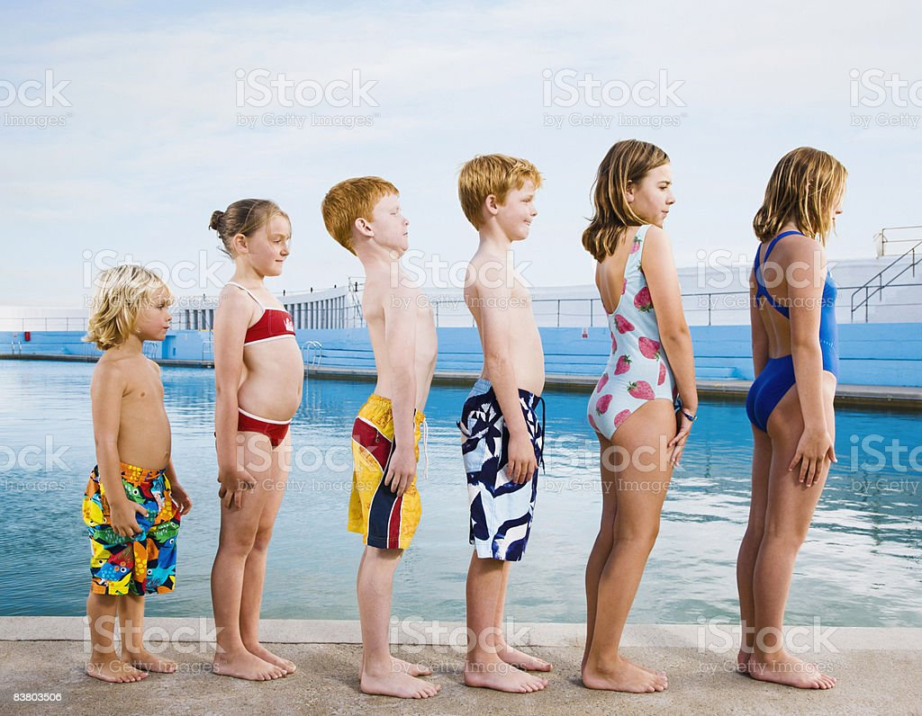 Line of children standing to attention by pool royalty-free stock photo