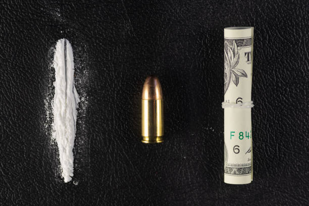 A line of cocaine powder, single bullet and dollar bill scroll on black surface A line of cocaine powder, a single 9 mm bullet and dollar bill scroll. Conceptual mockup of illegal drug dealing, trafficking, war on drugs. cocaine stock pictures, royalty-free photos & images