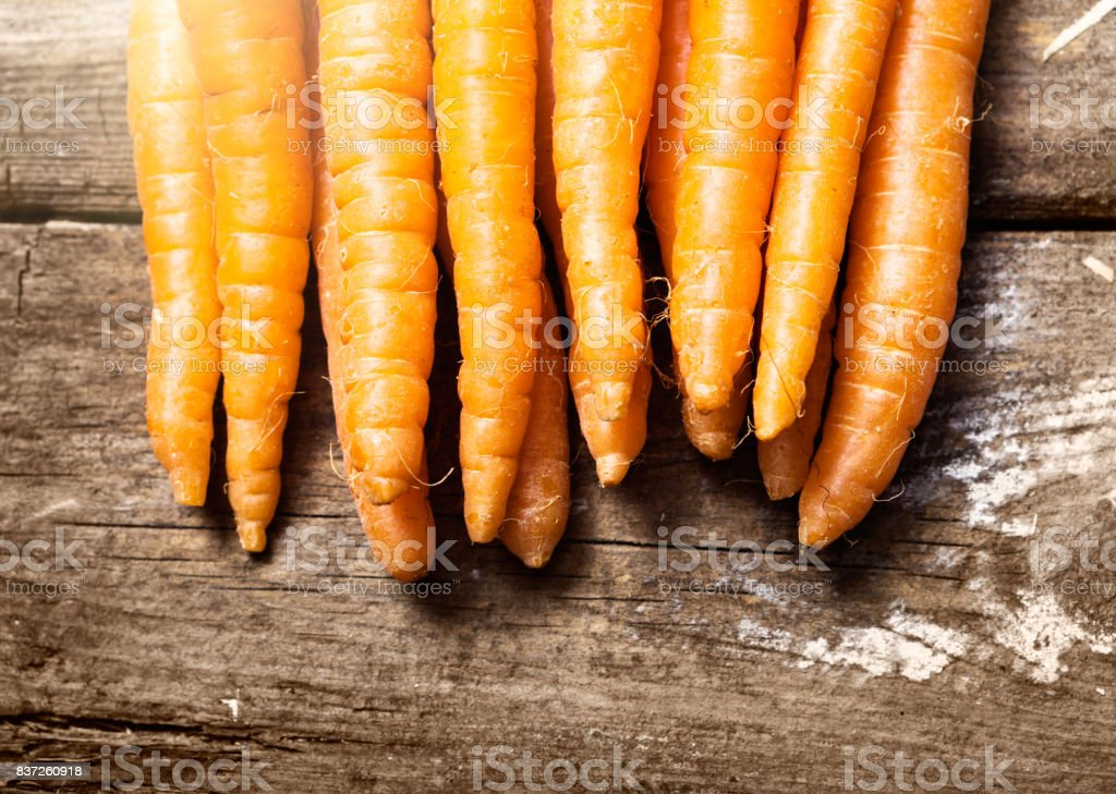 Line of crisp carrots dispayed on weathered wood stock photo