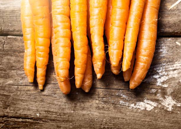 Line of crisp carrots dispayed on weathered wood stock photo