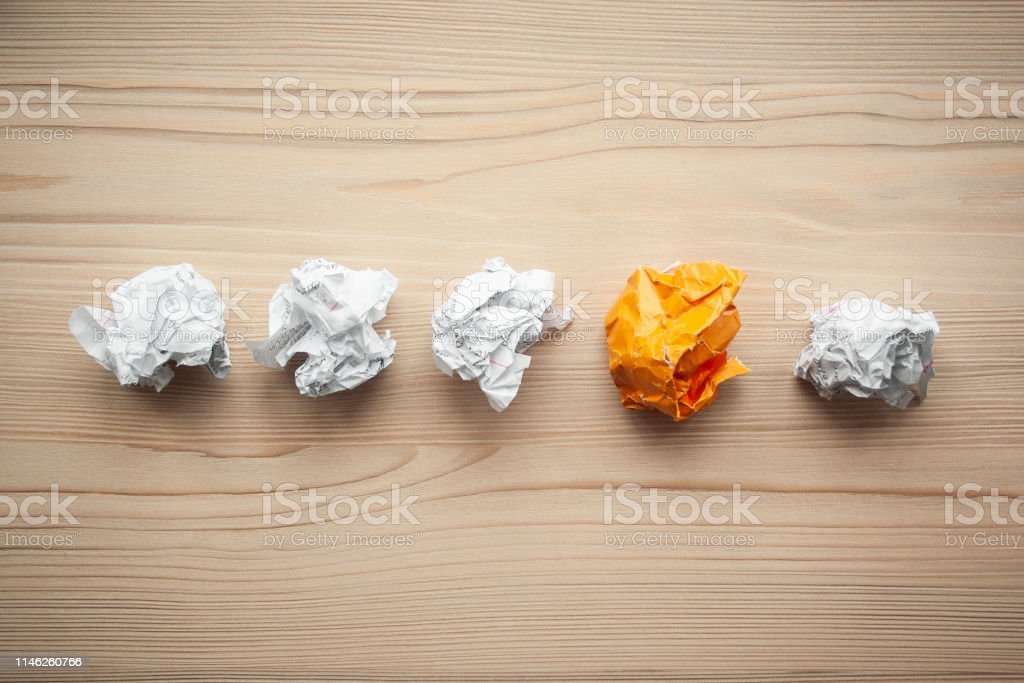 Line of crumpled white paper balls with one different orange paper...