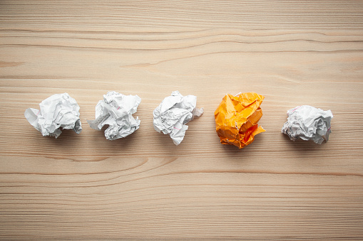 istock Line of crumpled white paper balls with one different orange paper ball between them. Concept of think different, think out of the box, leadership. 1146260766