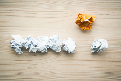 istock Line of crumpled white paper balls with one different orange paper ball above them. Concept of think different, think out of the box, leadership. 1146260781
