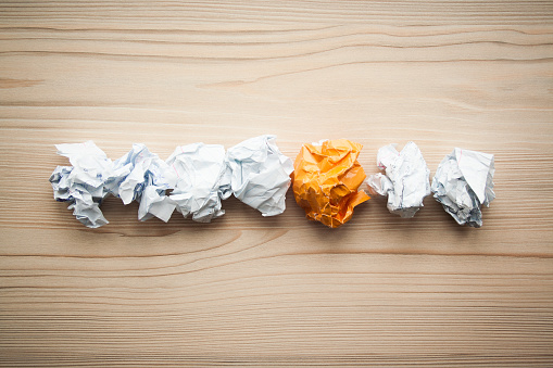 istock Line of crumpled white paper balls with one different orange paper ball between them. Concept of think different, think out of the box, leadership. 1146260782
