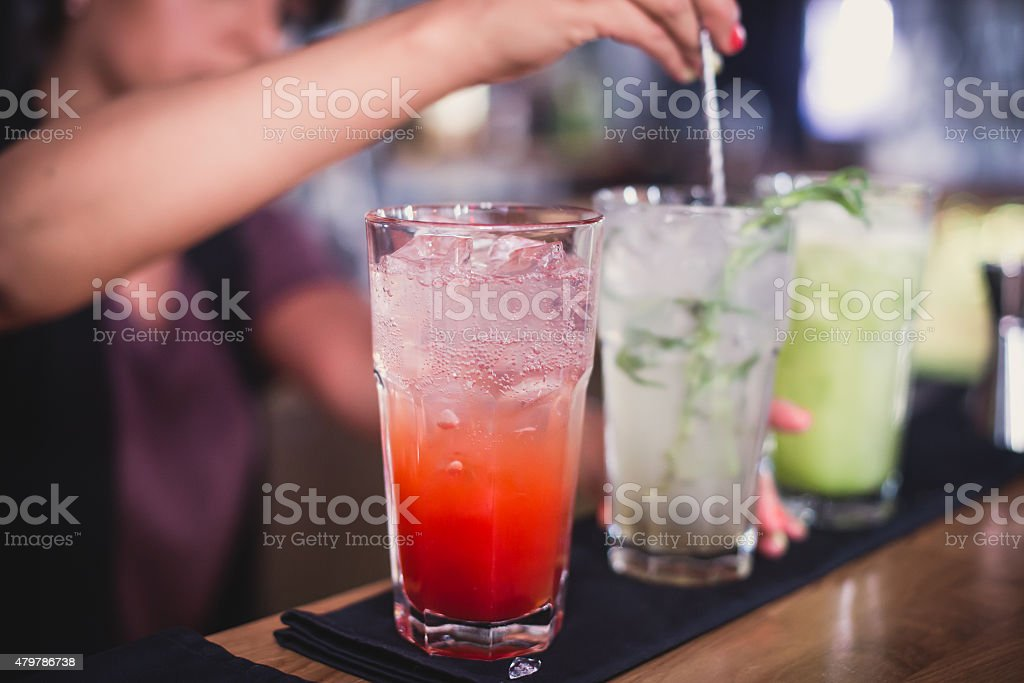 line of different coloured alcohol cocktails on a open-air party stock photo
