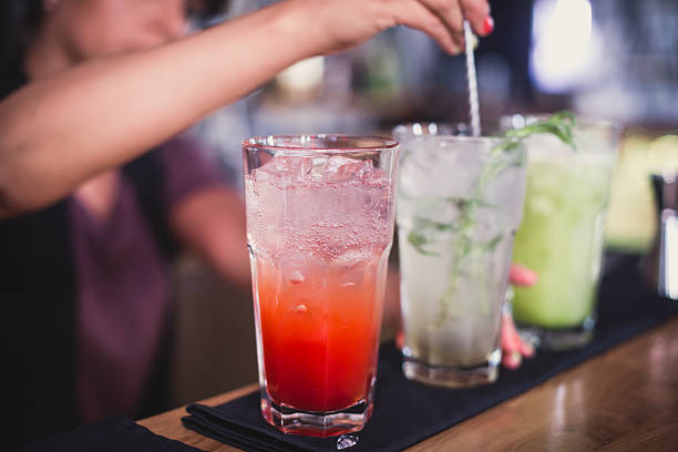 line of different coloured alcohol cocktails on a open-air party - happy hour stock photos and pictures