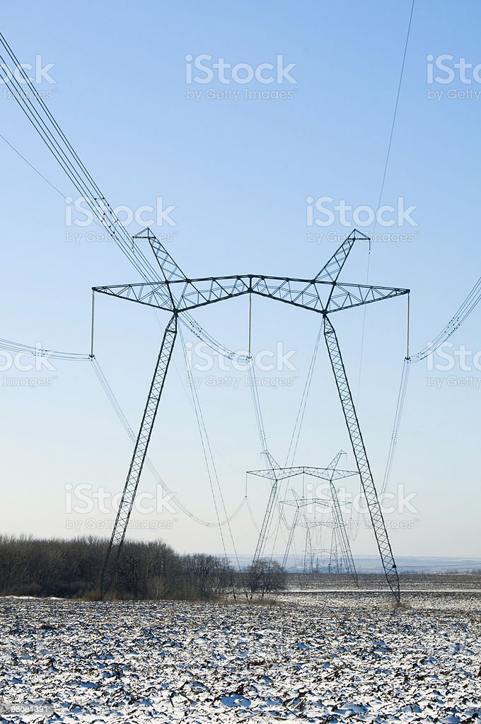 Linea di tralicci elettrici sul campo invernale foto stock royalty-free