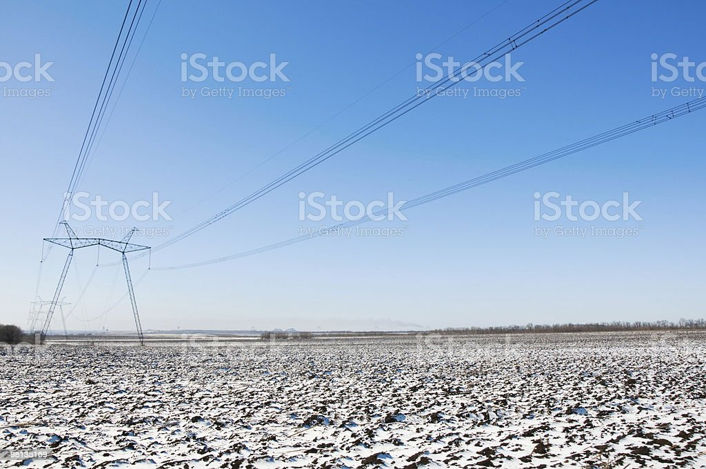 Line of electric pylons on winter field royalty-free stock photo