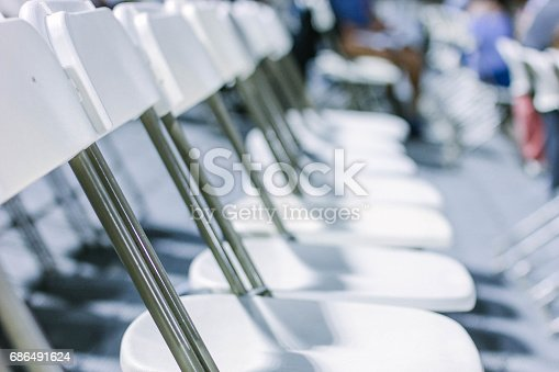 A line of empty foldable white chairs.