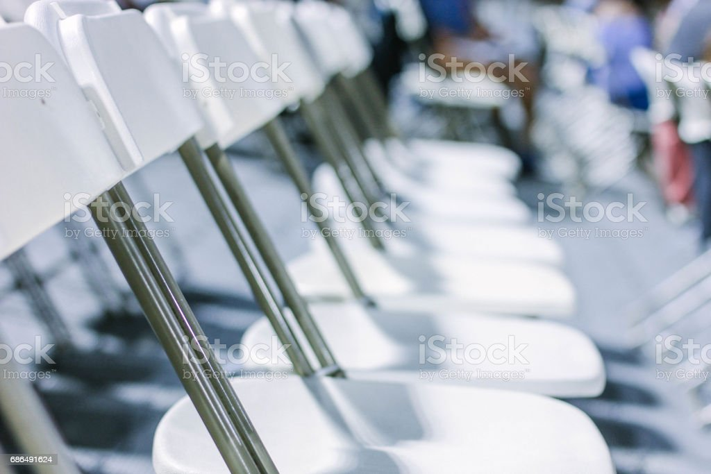 Line of empty foldable white chairs stock photo