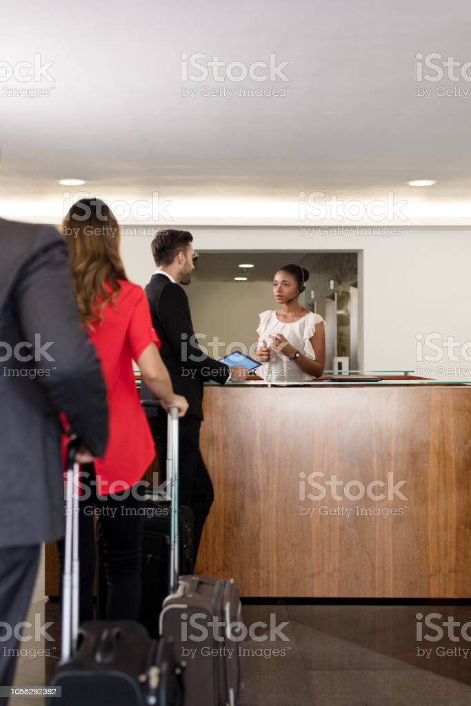 Line of executives waiting to talk with receptionist stock photo