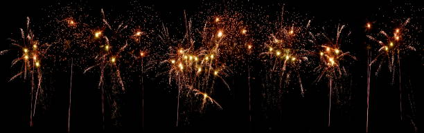 Line of fireworks crackling. Row of orange glitter accompanied by a succession of small explosions. pyrotechnic effects stock pictures, royalty-free photos & images