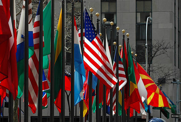 Line of flags from all different countries and nations The American flag stands out among others from around the world on display at Rockefeller Center in Manhattan diplomacy stock pictures, royalty-free photos & images