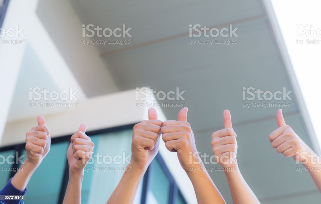 Line of group of human fists giving thumb up - office background - teamwork  business concept. stock photo