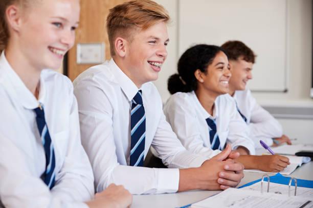 line of high school students wearing uniform sitting at desk in classroom - униформа стоковые фото и изображения