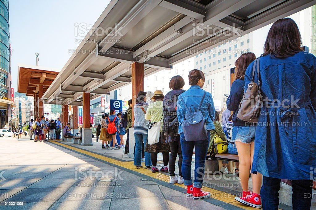 Line of Japanese people waiting for bus at Nagano station stock photo