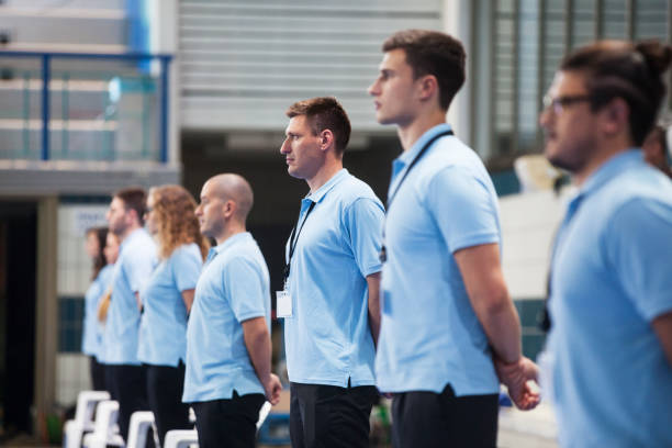 line of judges at a swimming tournament - judge sports official stock photos and pictures