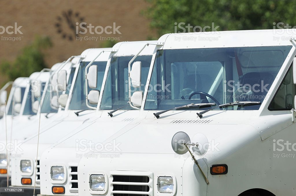 Line of mail carrier trucks parked under clock stock photo