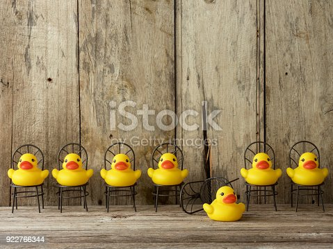 Line Of Many Yellow Rubber Ducks Sitting On Chairs Facing Towards ...