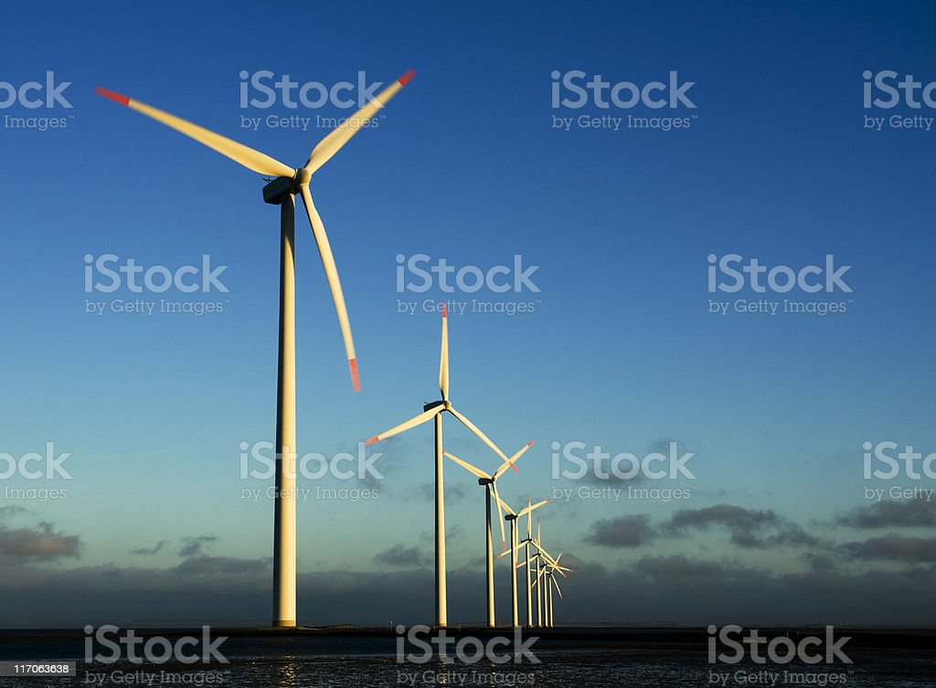 Line of modern windmills on a wind farm during sunset royalty-free stock photo