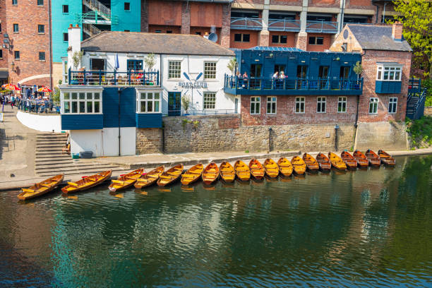 Line of moored rowing boats on the banks of River Wear near a boat club in Durham, United Kingdom on a beautiful spring afternoon. stock photo