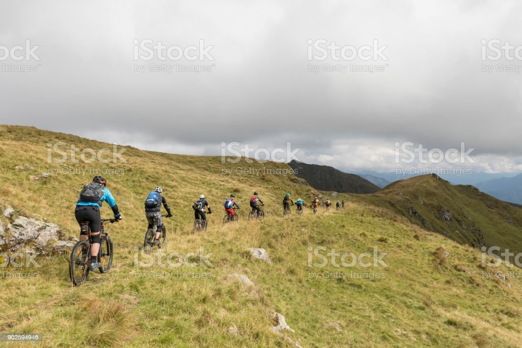 Line of mountainbikers on the downhill in the Friulian Mountains, Italy. stock photo