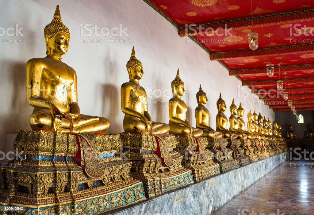 Line of multiple Golden Thai Buddha statues in lotus position stock photo