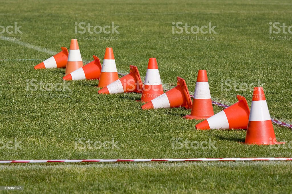 A line of orange and white cones on a green field