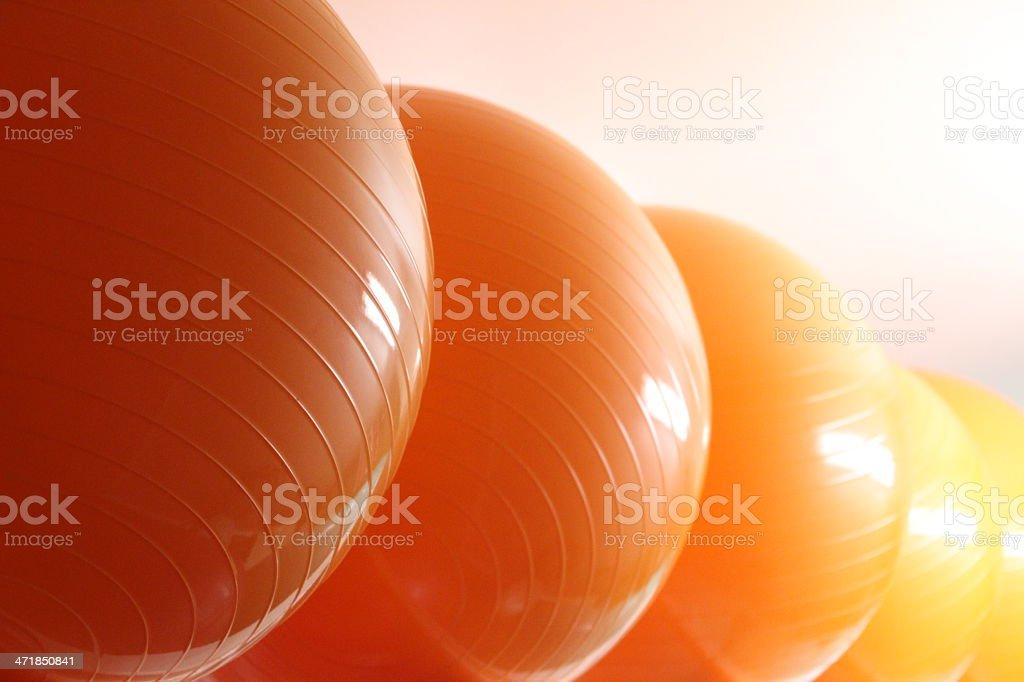 line of orange/yellow colored fitness balls stock photo