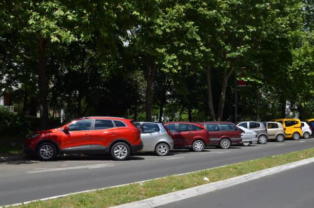 línea de coches aparcados - inmóvil fotografías e imágenes de stock