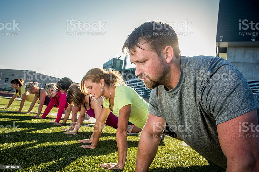 Line of people doing pushups outside on grass royalty-free stock photo