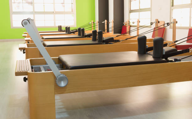 Line of pilates wood reformers in bright studio stock photo