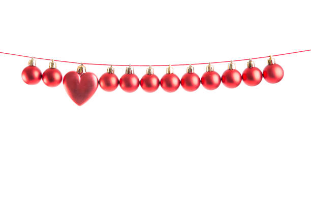 Line of red christmas balls and one heart shape christmas bauble on white background. Christmas decorations. stock photo