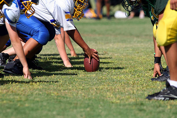 Line of Scrimmage American Youth Football player grips the ball at the line of scrimmage.  All logos and trademarks from cleats have been removed in Photoshop CS2 wide receiver athlete stock pictures, royalty-free photos & images