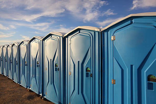 A line of several portable toilets set up in a grassy area Portable toilets portable toilet stock pictures, royalty-free photos & images
