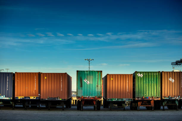 line of shipping containers on trucks - logistica foto e immagini stock