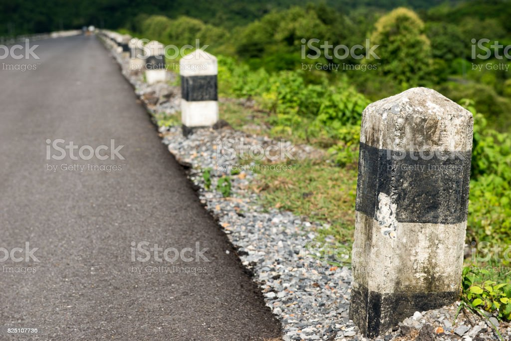 Line of stone bollards at side of asphalt road stock photo