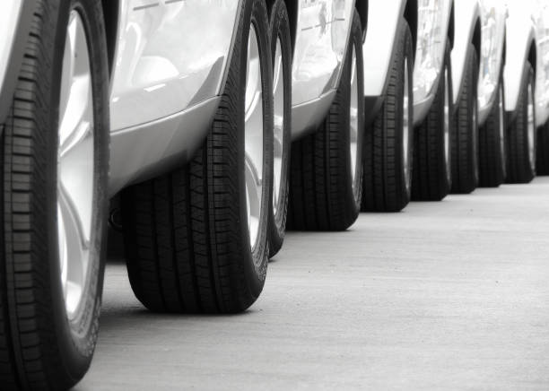 Line of the wheels of same vehicles staying on the road Wheels of new white cars laid out in lines on the asphalt caravan photos stock pictures, royalty-free photos & images