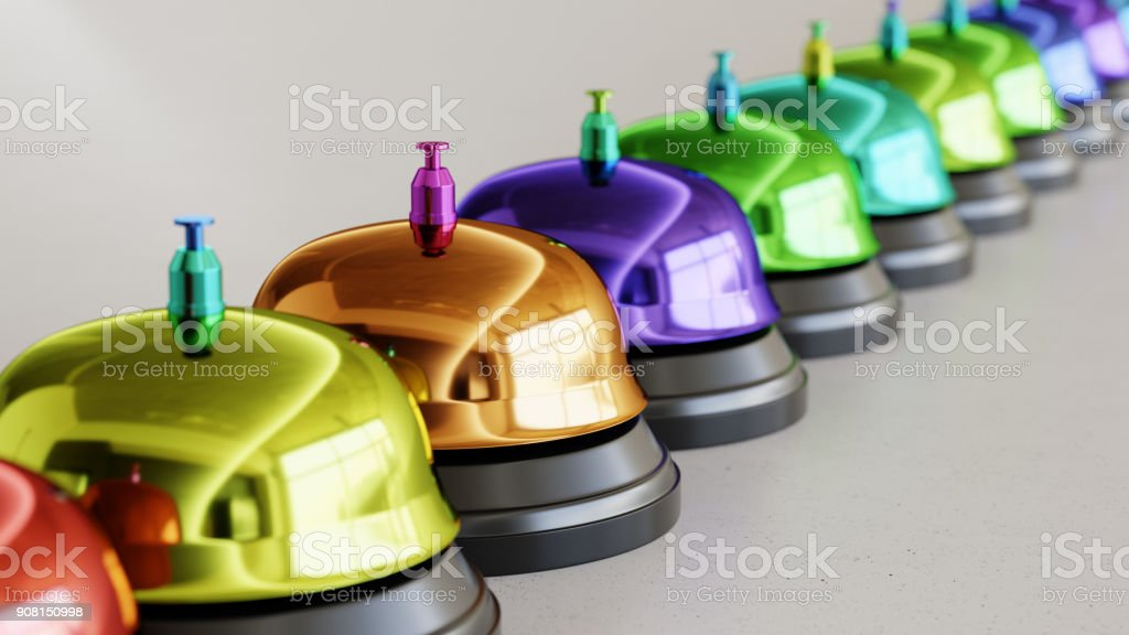 Line of Vibrantly Colored Reception Bells on Simple Light Grey Surface stock photo