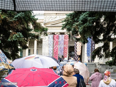 Moscow, Russia - July 31, 2019: line of visitors with umbrellas near Pushkin State Museum of Fine Arts in Moscow in rain. Pushkin Museum is the museum of European art, located in Volkhonka street