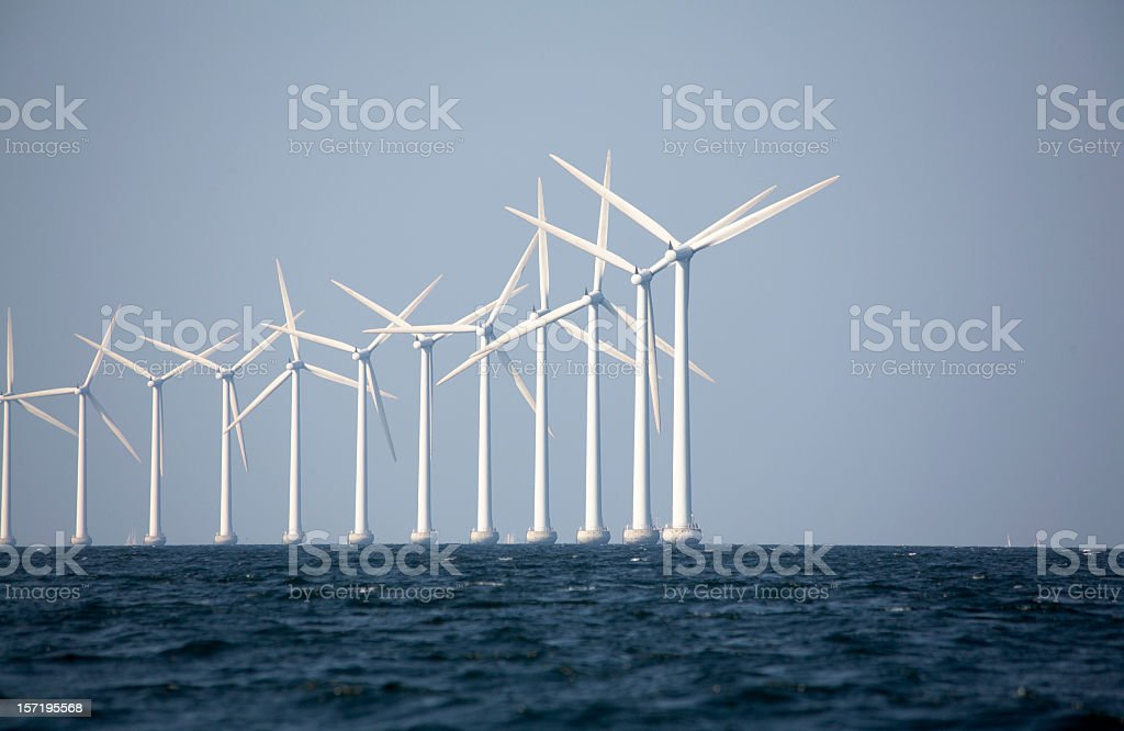 A line of wind turbines at an off-shore wind farm stock photo