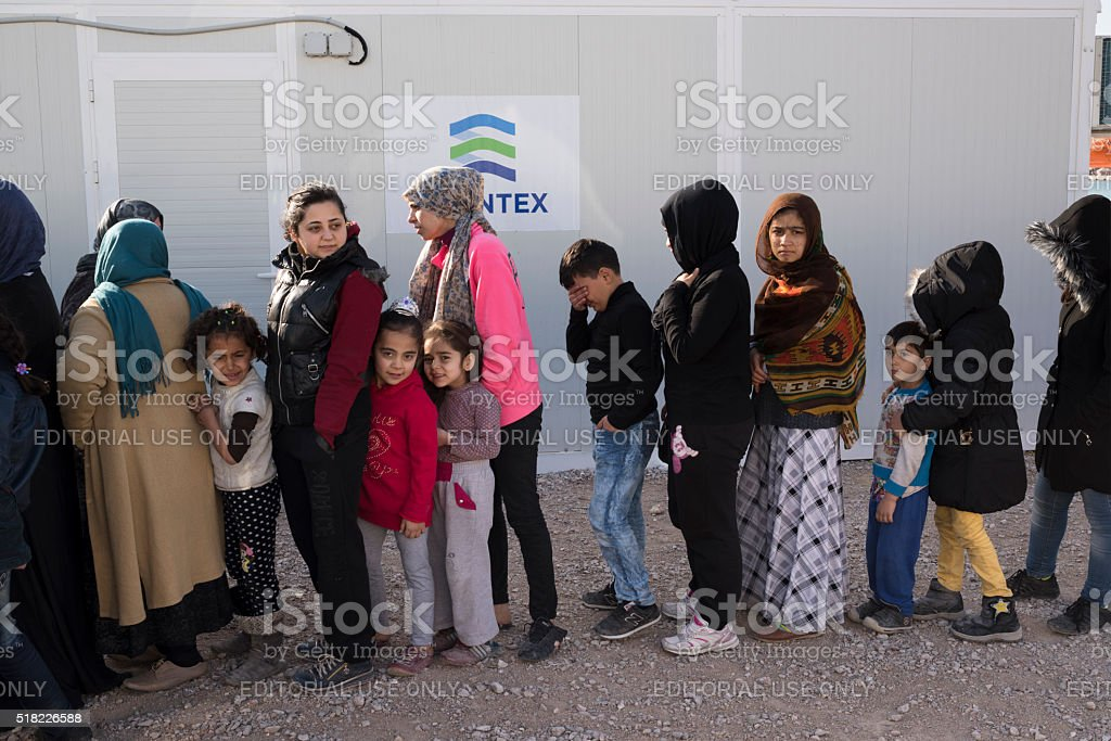 Line of women and children refugees waiting for breakfast stock photo