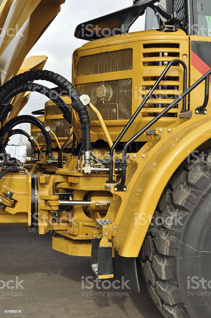 Line of Yellow Heavy Machinery Trucks royalty free stockfoto