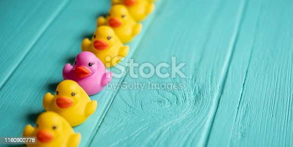 Line of yellow rubber ducks, moving in an orderly line, with one different purple duck standing out from the crowd within the line, set on a turquoise colored wooden grained background, conceptually representing water. Concept image representing; standing out from the crowd, individuality etc.