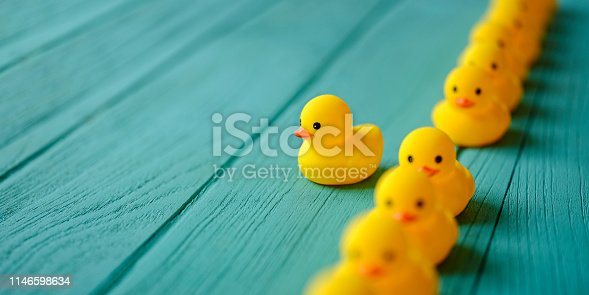 Line of yellow rubber ducks, moving in an orderly line, with one yellow duck breaking ranks moving out of the line following it's own direction, set on a turquoise colored wooden grained background, conceptually representing water. Concept image representing; standing out from the crowd, against the grain, freedom, individuality, against the grain, change, innovation etc.