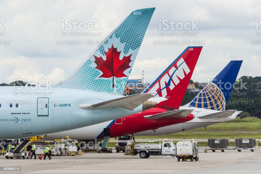 line up of three aircraft tails or vertical stabilizer Air Canada TAM Linhas Aereas and United Airlines at GRU Airport Sao Paulo International Brazil stock photo