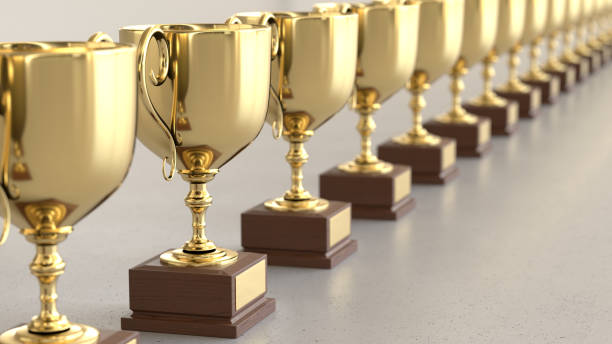 Linear Array of Gold Trophys on a Light Gray Surface Line of Gold Trophys on a simple light surface. This image is a 3d render. trophy award stock pictures, royalty-free photos & images