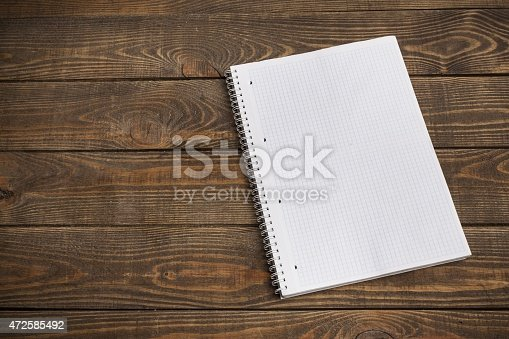 Area. Lined A4 ring bound pad on a double page spread rustic wooden background in portrait orientation with copy space to the left for insertion of your message, photographs or design elements.